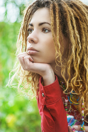 Young pensive beautiful woman with dreadlocks in red clothes closeup.