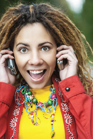 Young smiling beautiful woman with dreadlocks in red dress talking on two mobile phone. photo