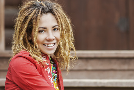 Young smiling beautiful woman with dreadlocks in red dress sitting on wooden bench. photo