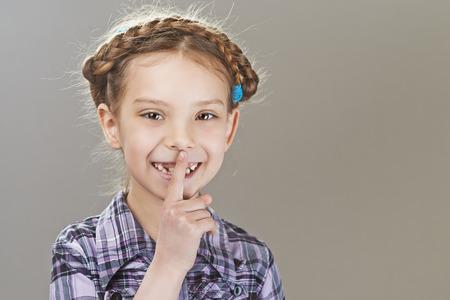 child finger: Happy girl-preschooler put finger to lips.