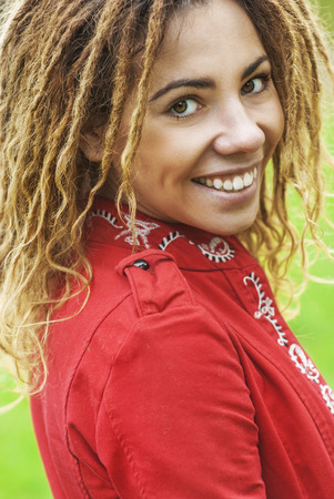 Young smiling beautiful woman with dreadlocks in red clothes closeup.