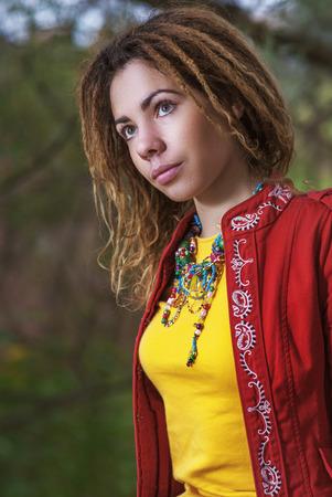 dreadlocks: Hermosa mujer sonriente joven con rastas en el vestido rojo sentado en el banco de madera.