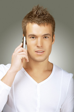 Smiling young man in white shirt talking on cell phone, on grey background. photo
