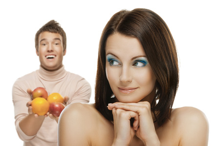 confused woman: portrait of beautiful smiling brunette man giving apple to confused happy woman