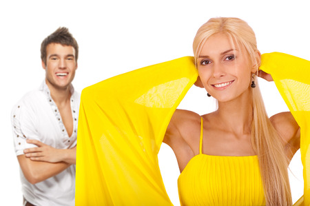 Two young people: smiling blonde woman and dark-haired man against white background. photo