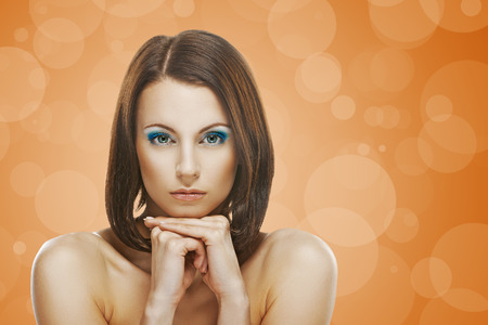 Portrait of beautiful young woman on orange background. photo