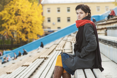Girl with red scarf at stadium autumn. photo