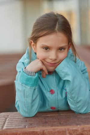 little finger: Beautiful little girl in blue jacket around school building.
