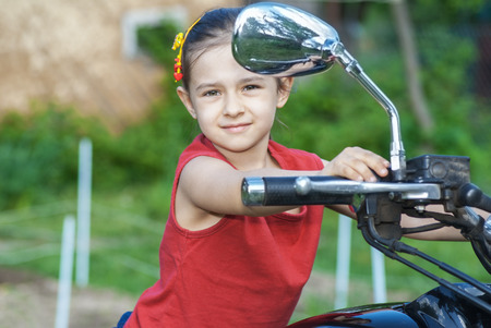 Little beautiful cheerful girl on old bike in park. Stock Photo