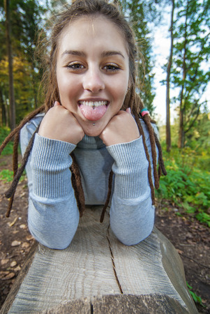 Young woman with dreadlocks lays on log in wood and tongue out. Stock Photo