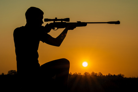 young man took aim with your sniper rifle at sunset. photo