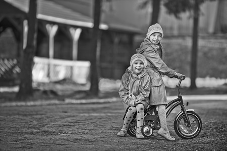Two little girls riding toy cycle on park. Stock Photo - 29811342