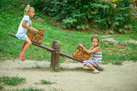 seesaw: Two sisters ride on swings against summer nature.