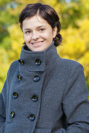 mackintosh: Portrait of beautiful smiling brunette girl against green park.