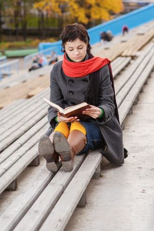 Beautiful young woman reads book on stadium tribune. photo