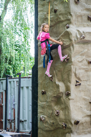 Little girl talking trains on climbing wall in summer city Park.. photo