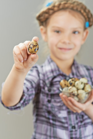 Portrait of beautiful little girl with quail eggs on gray background. photo