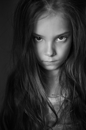 Mysterious little girl with long hair, black and white photography. Stock Photo