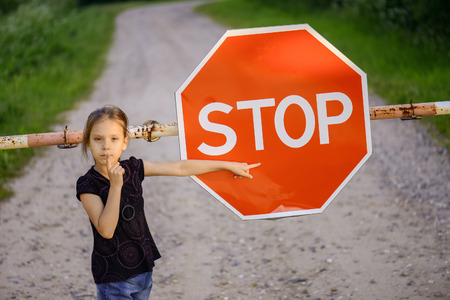 Beautiful little girl about red sign STOP. photo