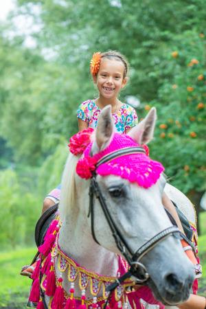 pony ride: Little girl riding festive horse in summer city Park. Stock Photo