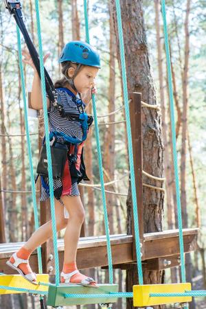 niño trepando: Hermosa niña se sube a la cuerda del arnés en el Parque de la ciudad de verano. Foto de archivo