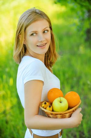 generoso: Retrato de joven tranquila hermosa rubia mujer sosteniendo cesta con frutas jugosas en el Parque de verano verde. Foto de archivo
