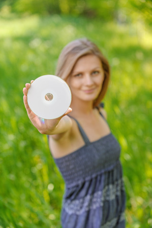 bluray: Young charming woman holds multimedia disk and smiles, in green summer city park.