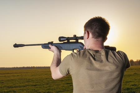 hombre disparando: joven apuntó con su rifle de francotirador sobre caminos rurales.