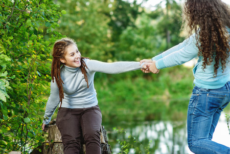 banisters: Two young and beautiful girls at banisters of little bridge in city-park. Stock Photo