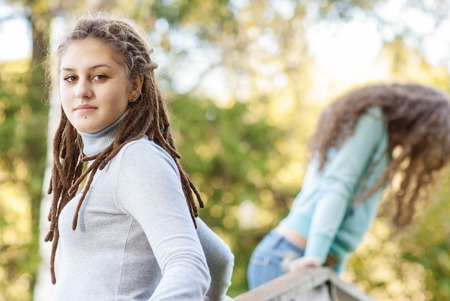 Two young and beautiful girls at banisters of little bridge in city-park. photo