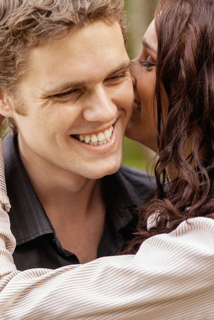 mid adult couple: Beautiful young girl whispers into ear of laughing man.