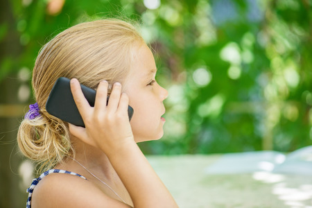 young girl smiling: Little girl talking on cell phone against green of Park in summer.