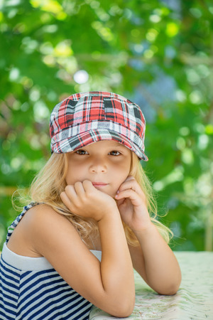 aslant: Little girl talking in plaid cap against green of the Park in summer.