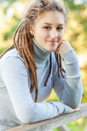 Young beautiful woman with hairdress dreadlocks against summer nature Stock Photo