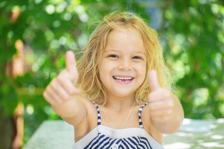 green thumb: Little cheerful girl lifts thumb upwards, on green background.