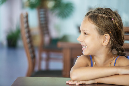 Beautiful little girl sitting at table and smiling. Stock Photo - 29086718