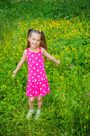 Portrait of beautiful smiling little girl in green summer city park. Stock Photo - 29086719