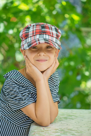 Little girl talking in plaid cap against green of the Park in summer. Stock Photo - 29086720