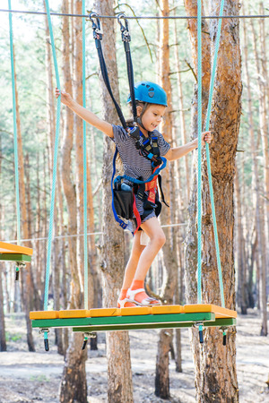 obstacle course: Little beautiful girl climbs on rope harness in summer city park.