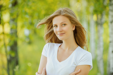 close-up portrait of beautiful young blond woman in white blouse at park holding her neck Stock Photo