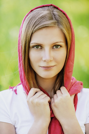 Close-up portrait of young joyous beautiful blonde woman wearing red headscarf and looking somewhere at summer green park. photo