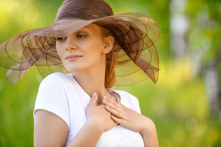 Close-up portrait of young nice smiling woman wearing brown fashionable hat at summer green park. Reklamní fotografie