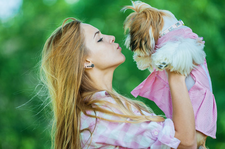 allegiance: Portrait of pretty, young, smiling woman holding small fluffy dog