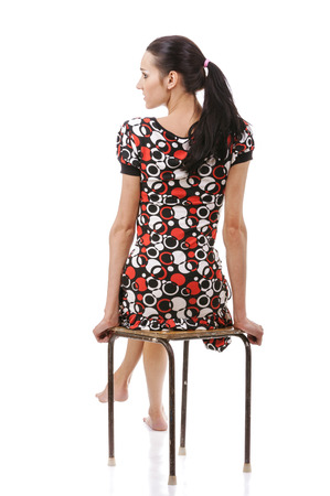 Beautiful young woman sitting on stool, isolated on white background.