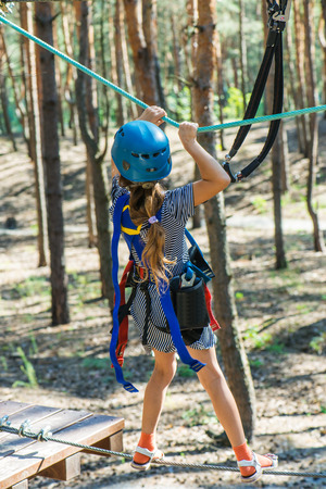 courageous: Little beautiful girl climbs on rope harness in summer city park.