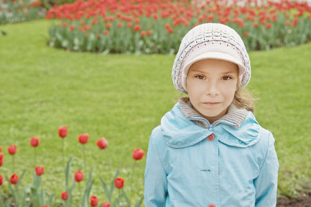 Portrait of pretty little girl in blue jacket in tulip park. Stock Photo - 29600157