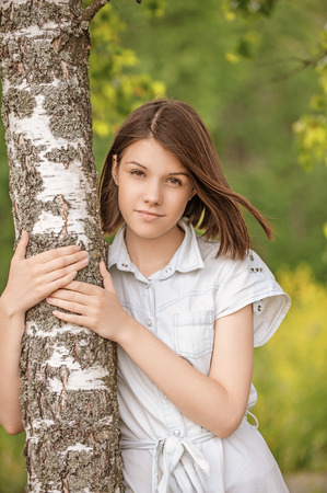 european white birch: Portrait of young attractive dark-haired woman wearing white chemise embracing birch tree at summer green park.