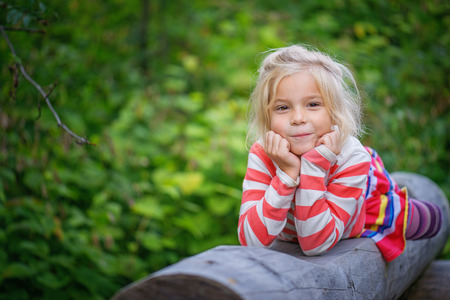 Portrait of beautiful smiling little girl lies on log in green city park. photo