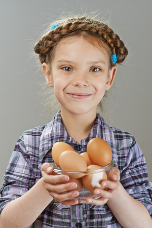 Little girl holding glass dish with chicken eggs, on gray background. Stock Photo - 29811588
