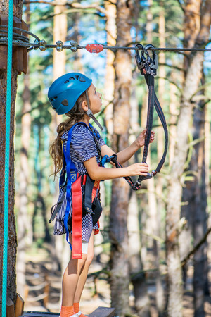 Little beautiful girl climbs on rope harness in summer city park. Stock Photo - 29811611